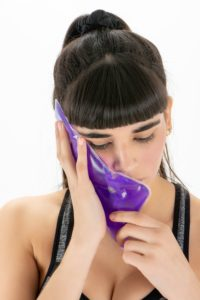 Woman with an ice pack on her cheek