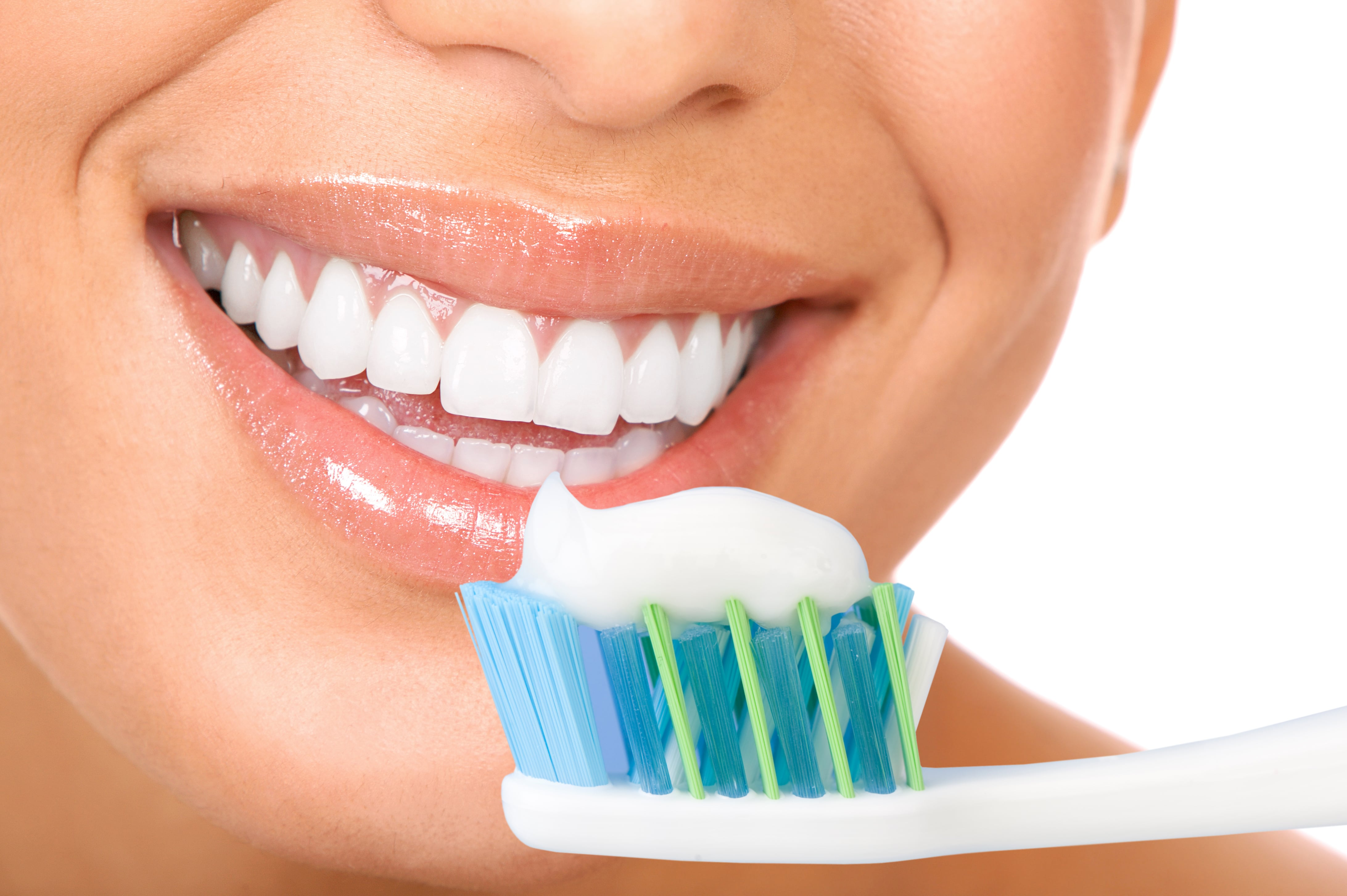 woman holding a toothbrush with toothpaste in front of her white smile