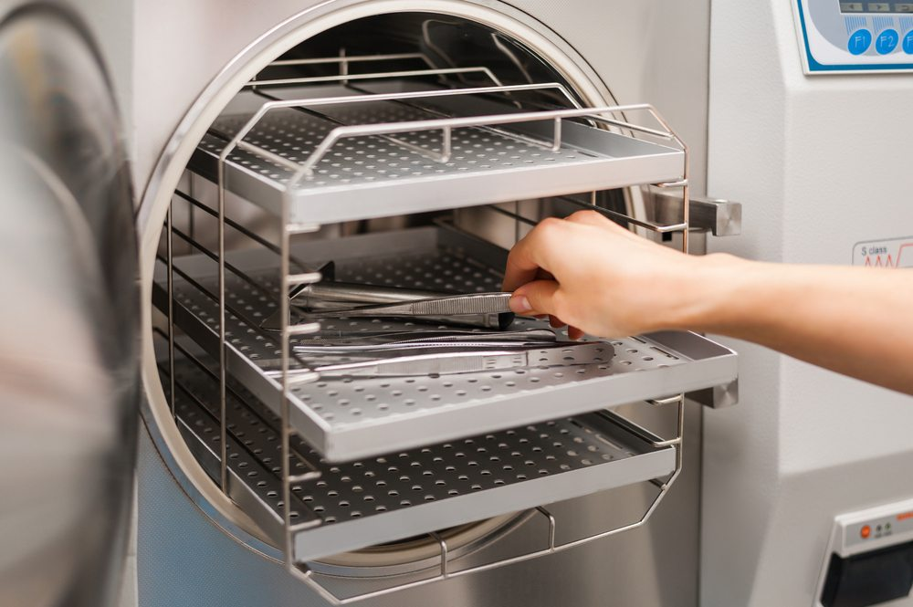 Dentist placing tools in heat sterilizer before use