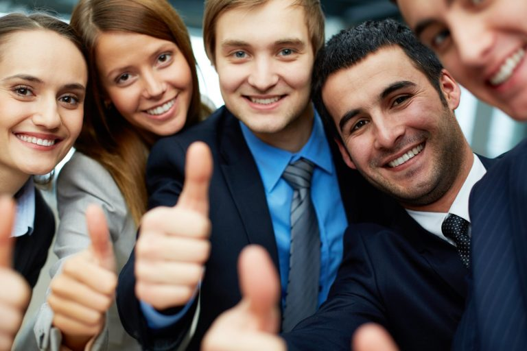 Five people dressed in business attire making thumbs up and smiling into the camera